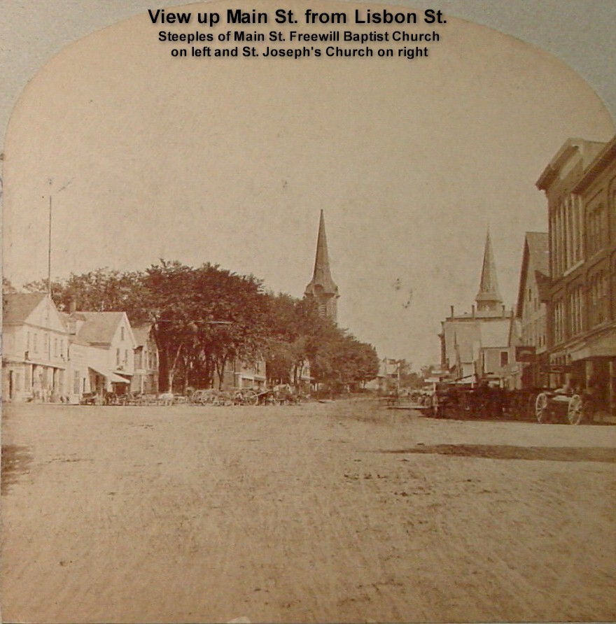 View up Main St. from Lisbon St. - Steeples of Main St. Freewill Baptist Church on left and St. Joseph's Church on right