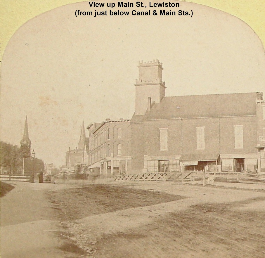 View up Main St. Lew. From just below Canal & Main Sts. The First Baptist Church on right burned in 1878 and replaced with the Masonic Temple.
