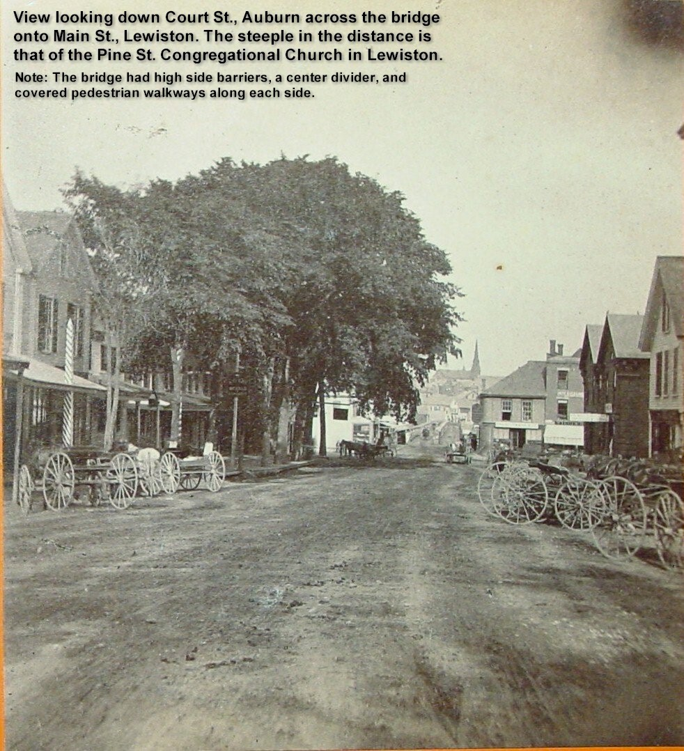 View looking down Court St., Auburn across the bridge onto Main St. Lewiston. The steeple of the Pine St. Congregational Church is visible